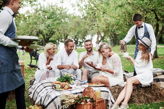 Serviço digno e divertido. grupo de amigos adultos descansam e conversam no quintal do restaurante na hora do jantar.