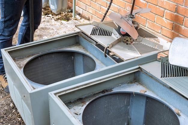 Serviço doméstico técnico com aletas de resfriamento do condensador do ar condicionado obstruídas