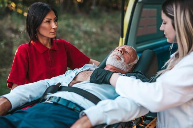 Serviço médico de emergência no trabalho. o paramédico está puxando a maca com um homem sênior com ataque cardíaco grave para o carro da ambulância. ajuda na estrada. conceito de assistência de motoristas.