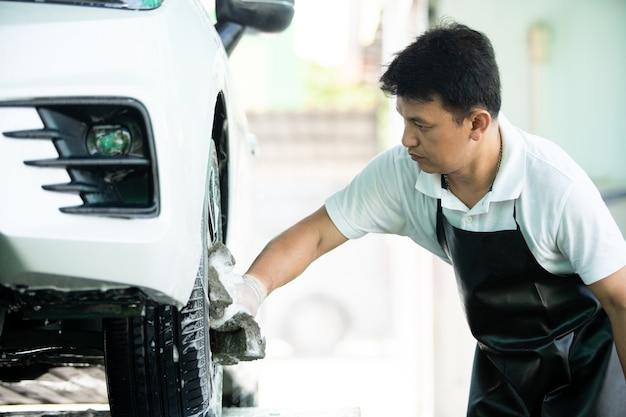 Serviço profissional de lavagem de carros, trabalhador asiático limpando e limpando pneus sujos de um veículo