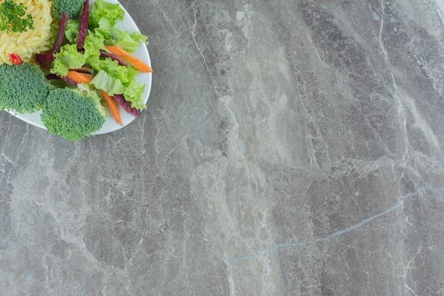 Serviço saudável de pilau com pimenta picada, repolho, verduras, cenoura e pedaços de brócolis em uma travessa sobre mármore.
