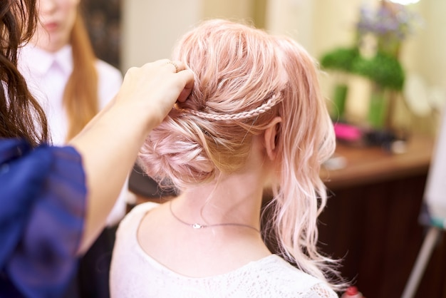 Serviços de cabeleireiro. criando um penteado à noite. processo de estilo de cabelo.