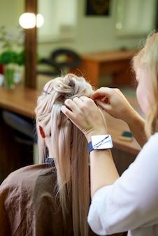 Serviços de cabeleireiro. сreating um penteado de noite. processo de estilo de cabelo.