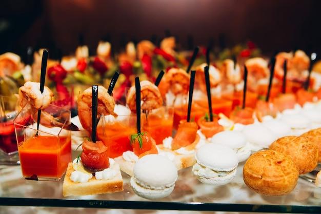 Serviços de catering. buffet com frutos do mar. canapés com peixe vermelho, molho de camarão, pequenos sanduíches.