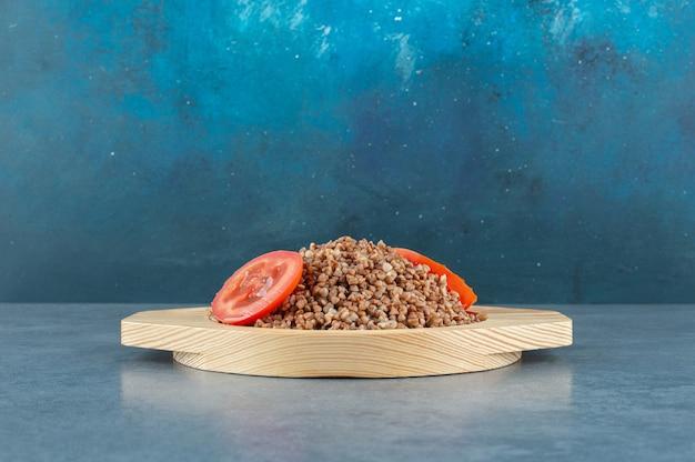 Servida saborosa de trigo sarraceno cozido num prato de madeira, coberto com rodelas de tomate, sobre fundo azul. foto de alta qualidade