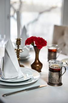 Servido à mesa com um copo de chá em uma xícara retrô
