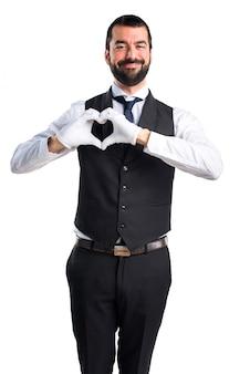 Servidor de luxo fazendo um coração com as mãos