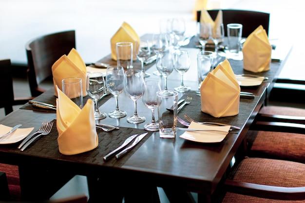 Servindo a mesa no restaurante com taças de vinho e talheres
