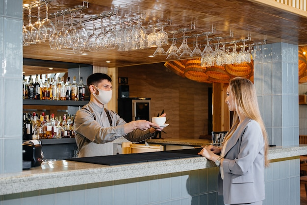 Servindo a um barista mascarado um delicioso café natural para uma jovem em um belo café durante uma pandemia.