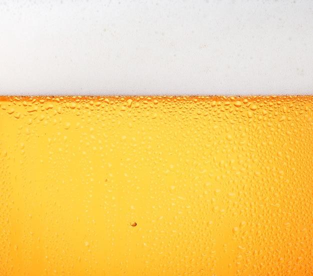 Servindo cerveja lager com bolhas e espuma em um copo gelado
