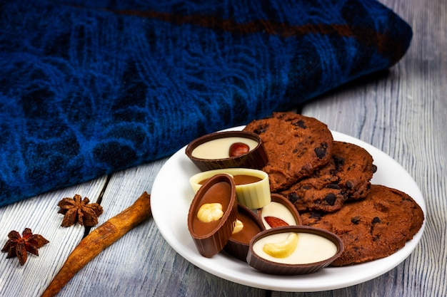 Servindo chocolates e biscoitos caseiros em uma mesa de luz.