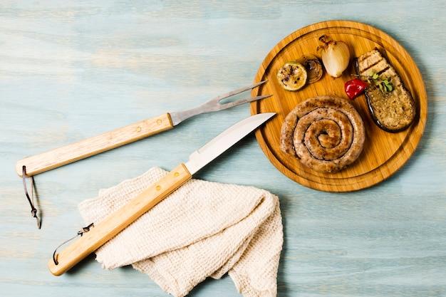 Servindo de salsichas e legumes grelhados