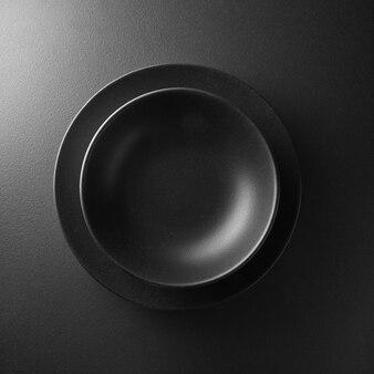 Servindo dois pratos pretos no fundo preto