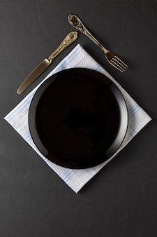 Servindo em um restaurante luxuoso. prato vazio preto e utensílios de prata.