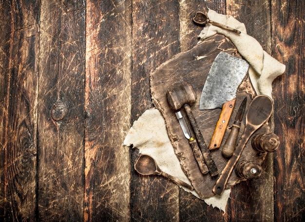 Servindo fundo. placa de corte de utensílios de cozinha antigos. em uma mesa de madeira.