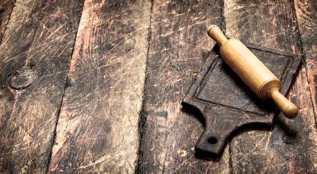 Servindo fundo. rolo de massa em uma placa de corte. em uma mesa de madeira.