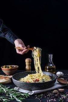 Servindo massas italianas da panela, copie o espaço. refeição tradicional de espaguete com legumes e azeitonas na superfície rústica preta