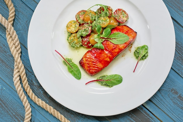 Servindo prato salmão grelhado com legumes, manjericão, tomate e molho.
