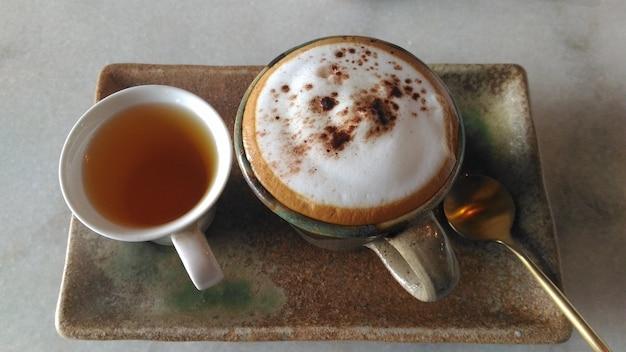 Servindo uma xícara de cappuccino quente com uma xícara de chá chinês quente.