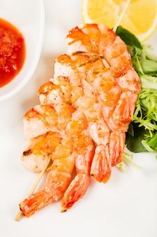 Servir camarão quente no espeto com molho
