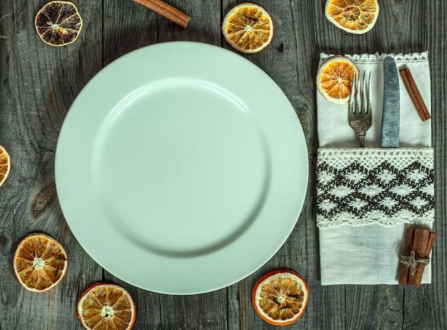 Serviu prato vazio branco sobre uma superfície de madeira cinza