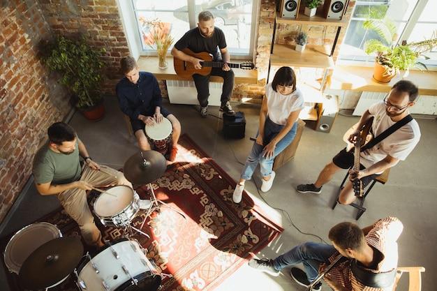 Sessão. banda de músicos tocando juntos no local de trabalho de arte com instrumentos. homens e mulheres caucasianos, músicos, tocando e cantando juntos. conceito de música, hobby, emoções, ocupação artística.