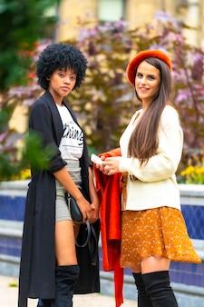 Sessão de estilo de vida. duas boas amigas visitando a cidade, uma morena e uma garota latina