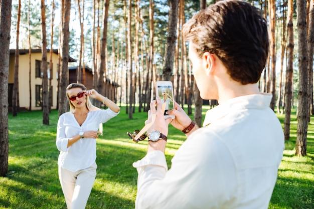 Sessão de fotos da natureza. homem bom e inteligente segurando um smartphone enquanto tira uma foto da namorada