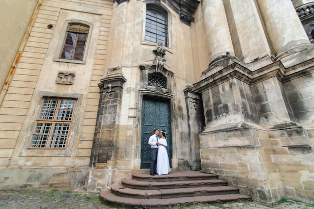 Sessão de fotos de casamento no fundo da igreja velha. a noiva e o noivo se abraçam. fotografia de casamento em estilo rústico ou boho