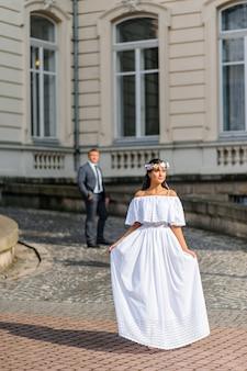 Sessão de fotos de casamento no fundo do edifício antigo. o noivo observa a noiva posando. fotografia de casamento rústico ou boho.