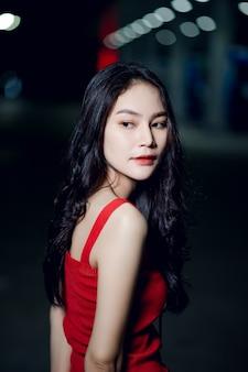 Sessão de fotos de menina bonita como no vestido vermelho à noite