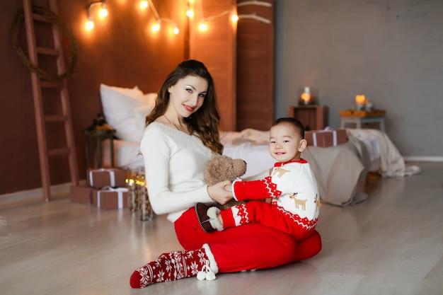 Sessão de fotos de natal de uma família de dois uma mãe e uma criança 2-3 anos