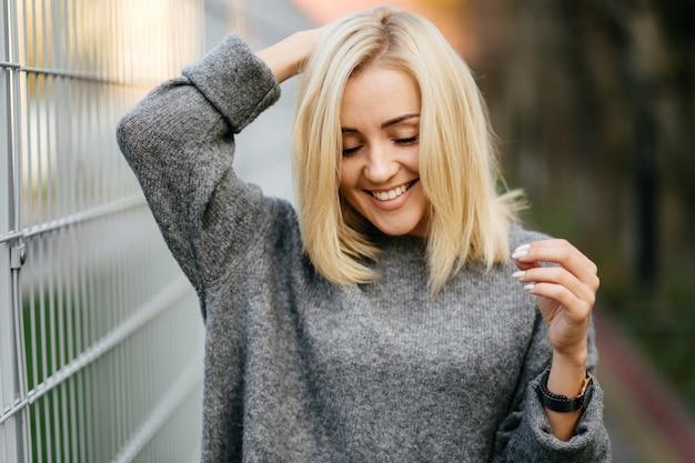 Sessão de fotos de rua moda jovem elegante em uma roupa cinza