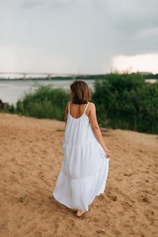 Sessão de fotos de verão de uma garota em um vestido branco na areia. verão