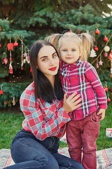 Sessão de fotos em família, ano novo, de mãe e filha em julho, perto da árvore de natal com presentes no parque