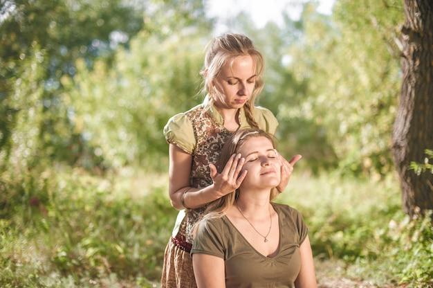 Sessão de massagem. o profissional de massagem demonstra métodos de massagem refrescantes na grama.