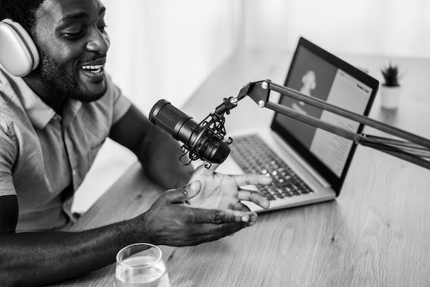 Sessão de podcast de transmissão ao vivo de homem africano em estúdio caseiro - foco no microfone