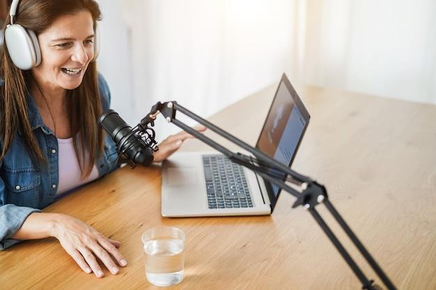 Sessão de podcast de transmissão ao vivo para mulher idosa em estúdio caseiro - foco principal no microfone