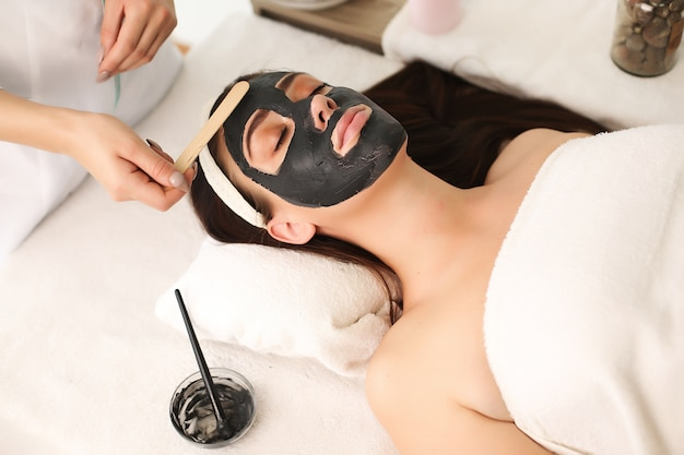 Sessão de tratamento facial no centro de spa com uma linda mulher