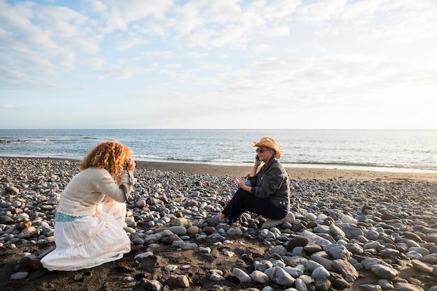 Sessão fotográfica com duas mulheres. um fotógrafo e uma mulher madura falando ao telefone para representar um estilo de vida agradável na praia. estoque e conceito de publicidade funcionam