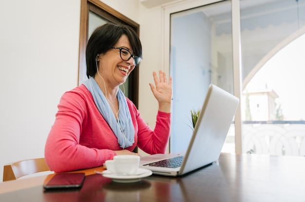 Sessenta anos de idade professora usando fones de ouvido, tendo aula on-line através de chat por vídeo no computador portátil. ela está sentada em uma mesa moderna de madeira em casa.