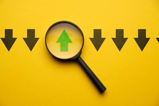 Seta abstrata em uma lente de aumento em um espaço amarelo - o conceito pensa diferentemente.