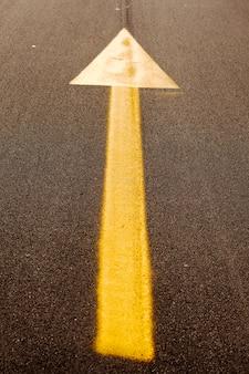 Seta amarela no asfalto