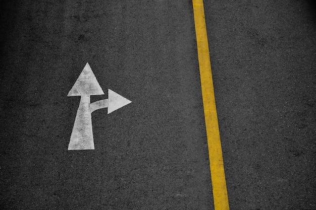 Seta branca pintada na estrada de asfalto (siga em frente e vire à direita)