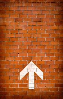 Seta branca pintada na parede de tijolos