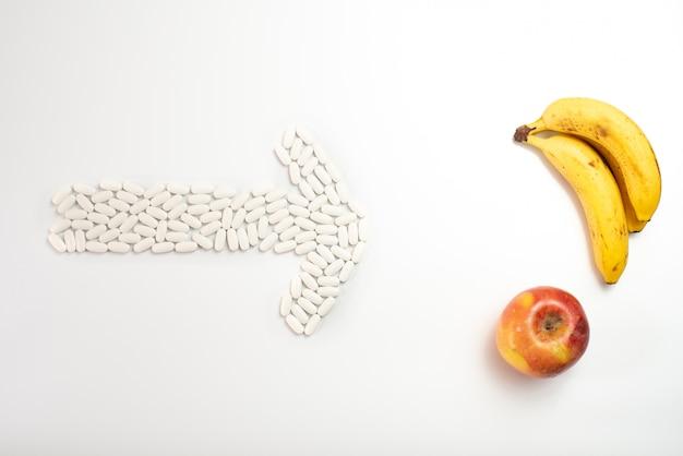 Seta com comprimidos que apontam um fruto contra suplementos, conceito da nutrição saudável.
