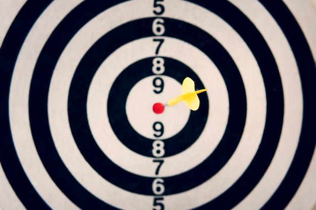 Seta de dardo acertando o alvo do alvo de dardos em fundo branco. atingindo o alvo. objetivo claro. arremesso de dardo certeiro. o verdadeiro golpe de um atirador. um tiro no alvo. atingindo o alvo com um lançamento de dardo.