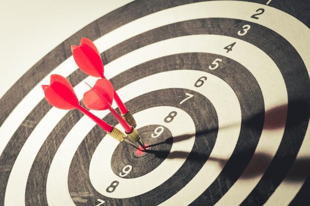 Seta de dardo que bate no centro de alvo de dartboard. conceito do sucesso