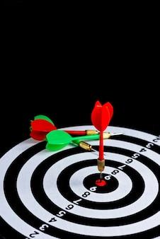 Seta de dardo vermelha e verde atingindo o centro do alvo. mesa de dardo isolada em fundo preto,