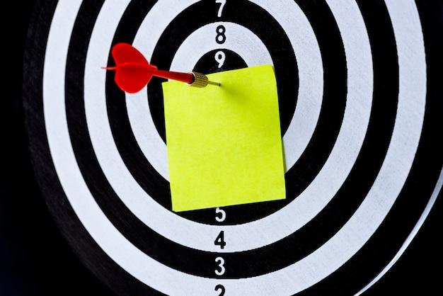 Seta de dardo vermelho, atingindo o centro do alvo com notas em branco no tabuleiro de dardo